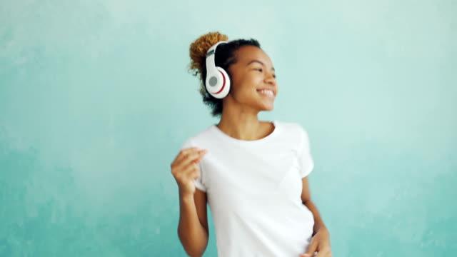 Retrato-de-mujer-afroamericana-feliz-escuchando-música-con-auriculares-inalámbricos-y-bailar-disfrutando-de-la-melodía-Tecnología-moderna-el-concepto-de-gente-y-diversión-