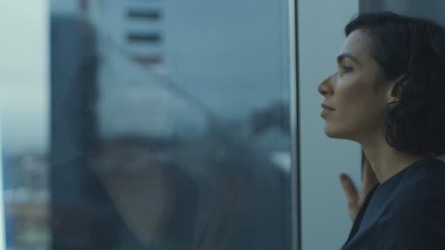 Close-up-retrato-de-la-hermosa-joven-empresaria-mirando-cuidadosamente-fuera-de-su-ventana-de-la-oficina-con-vista-al-paisaje-urbano-Mujer-hispana-confiada-y-atractivo-pensando-en-su-proyecto-empresarial-