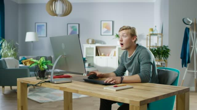 Portrait-von-der-hübsche-Mann-arbeiten-am-PC-hat-Glücksfall-emotional-feiert-Sieg-dadurch-Luft-Punch-Im-Hintergrund-stilvolle-gemütliche-Wohnzimmer-Zoomen-Sie-In-Schuss-