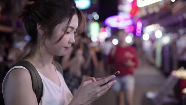 Asian-woman-tourist-backpacker-smiling-and-using-smartphone-traveling-alone-holidays-outdoors-on-city-street-in-Khao-San-road-at-Bangkok-Bangkok---Thailand-