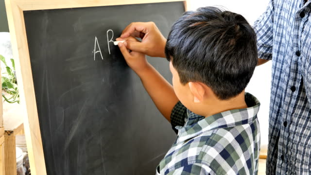 Father-teaches-children-boy-to-writing-the-chalkboard-Education-concept-