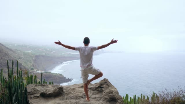 A-man-standing-on-one-hand-in-the-mountains-with-his-back-to-the-camera-looking-at-the-ocean-and-meditating-on-the-Canary-Islands-