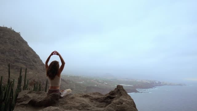 A-woman-sitting-on-top-of-a-mountain-meditates-and-makes-a-gesture-with-her-hands-Maha-Sakal-Against-the-ocean-and-green-mountains
