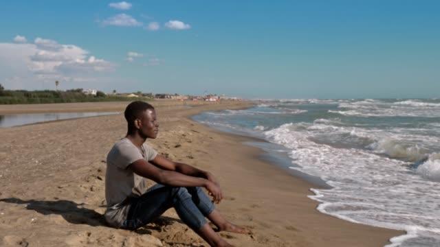solitario-negro-africano-joven-sentado-en-la-playa-contemplando-el-mar