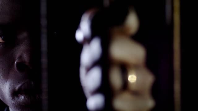 Young-african-prisoner-behind-bars-staring-at-camera-Criminal-prison-law