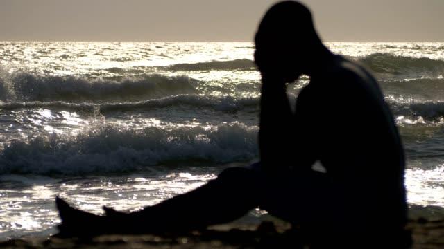 Migración-desesperación-Silueta-de-hombre-triste-sentado-en-la-playa