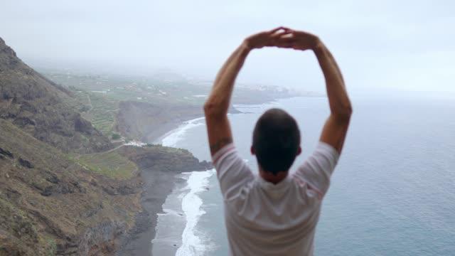 Der-Mann-steht-am-Rand-einer-Klippe-in-der-Pose-des-Hundes-mit-Blick-auf-den-Ozean-genießen-die-Seeluft-während-einer-Yoga-Reise-durch-die-Inseln