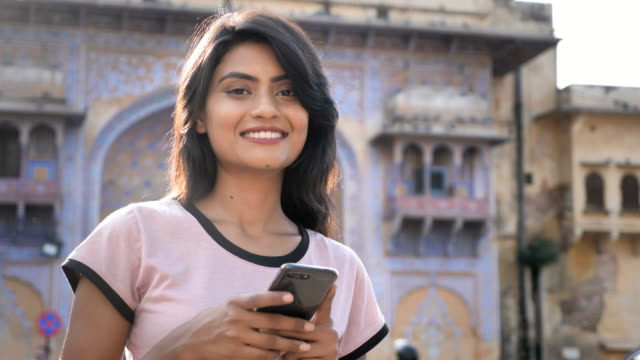 An-attractive-girl-using-smartphone-or-cellphone-is-smiling-looking-at-the-camera