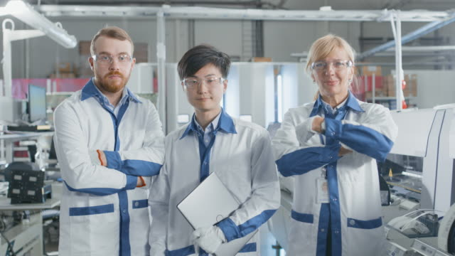 On-High-Tech-Factory:-Portrait-of-Three-Professional-Engineers-In-the-Background-Electronic-Printed-Circuit-Board-Assembly-Line-that-Uses-Surface-Mount-Technology-and-Pick-and-Place-Machinery-