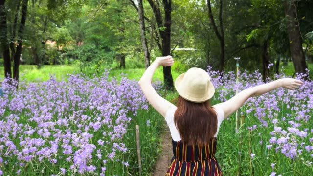 Back-view-of-woman-happily-raising-hands-up-and-walking-in-purple-flower-field-during-day-time---Flowers-of-orchid-lavender