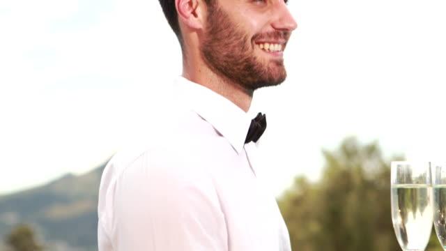 Smiling-waiter-holding-champagne-glasses