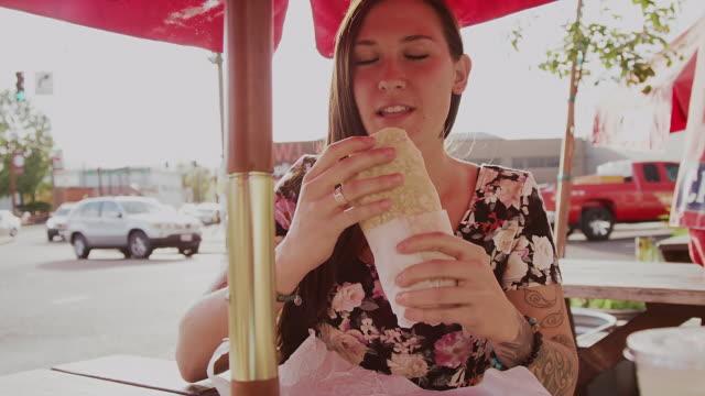 Ein-Schönes-Mädchen-ein-einem-Tisch-im-Freien-essen-ein-Burritos-Zeitlupe