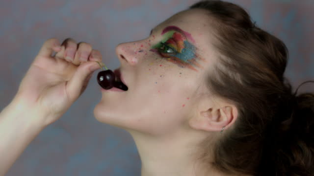 4k-Shot-of-a-Woman-with-Multicoloured-Make-up-Eating-Cherry