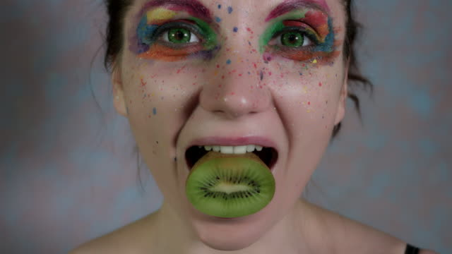 4k-Shot-of-a-Woman-with-Multicoloured-Make-up-Squeezing-a-Kiwi-in-Mouth