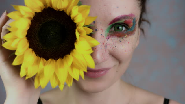 4k-Shot-of-a-Woman-with-Multicoloured-Make-up-With-Sunflower-(focus-on-eye)