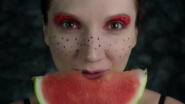 4k-Shot-of-a-Woman-with-Multicoloured-Make-up-Eating-a-Watermelon