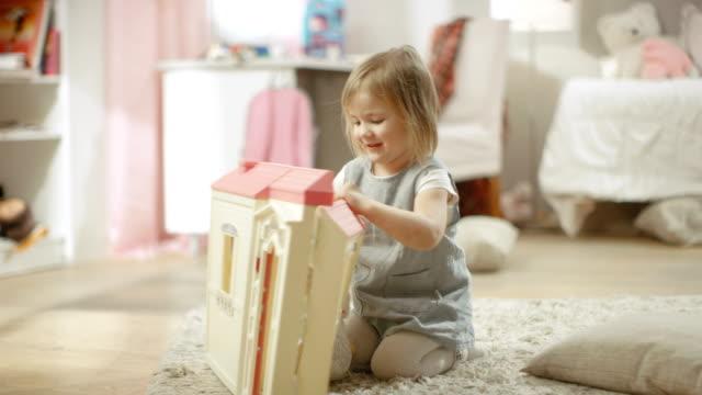 Feliz-niña-corre-hacia-casa-de-muñecas-y-comienza-a-jugar-con-él-