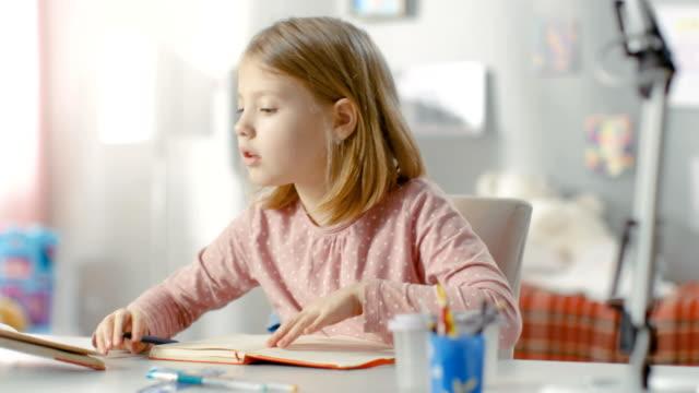 Smart-Little-Girl-Does-Homework-in-Her-Room-
