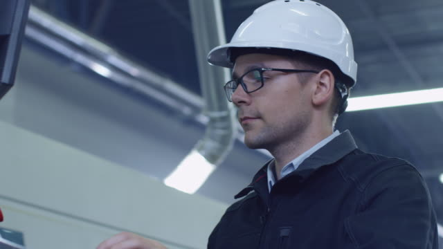Engineer-in-Hard-Hat-Setting-Up-CNC-Machine-at-the-Factory