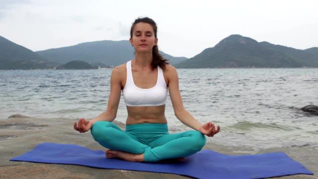 Mujer-joven-practicar-yoga-en-la-playa-al-atardecer-