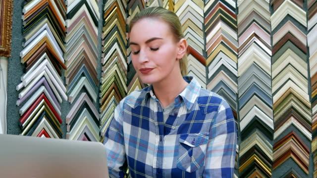 Retrato-de-un-joven-empresario-mujer-tras-el-mostrador-usando-la-computadora-portátil-en-su-tienda
