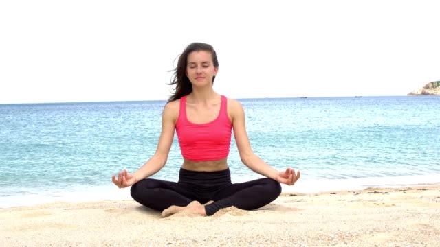 Joven-practicando-yoga-en-la-playa-al-atardecer-Ejercicios-de-tranquilidad-y-armonía-Meditación-en-postura-de-loto-Estilo-de-vida-saludable-