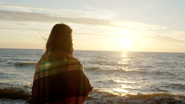Back-view-of-the-brunette-woman-standing-on-the-shore-of-sea-and-dreaming-Young-female-enjoying-the-beach-and-sunset