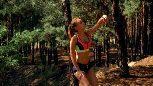 sport-girl-with-elastic-tummy-stands-in-the-Woods-and-looks-to-your-phone