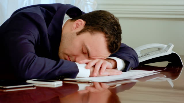 Tired-businessman-awakened-by-phone-call-and-answer