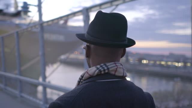 Joven-negro-a-hombres-con-gafas-de-sol-sombrero-y-bufanda-Disfrutar-el-día-al-aire-libre-en-la-ciudad