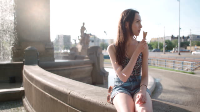 Young-beautiful-woman-eating-ice-cream-during-sunny-day-outdoors-