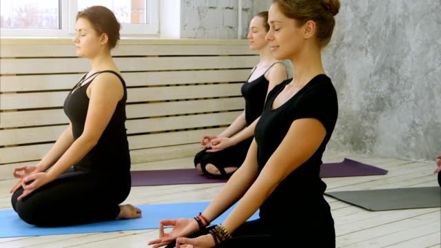 Hermosas-mujeres-jóvenes-trabajando-en-interior-de-loft-haciendo-yoga-exercis-meditando-con-el-gesto-de-la-mano-de-mudra
