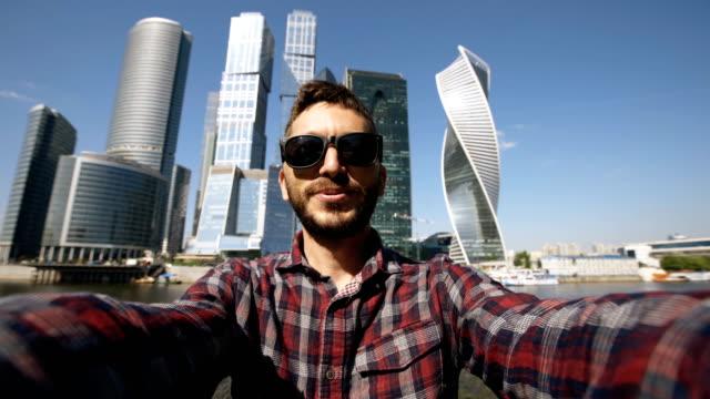 Happy-Tourist-Mann-mit-online-video-Chat-mit-seinem-Smartphone-Kamera-in-der-Nähe-von-internationalen-Business-Center-in-Moskau