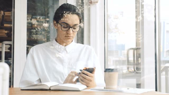 Mujer-joven-con-teléfono-y-hacer-notas