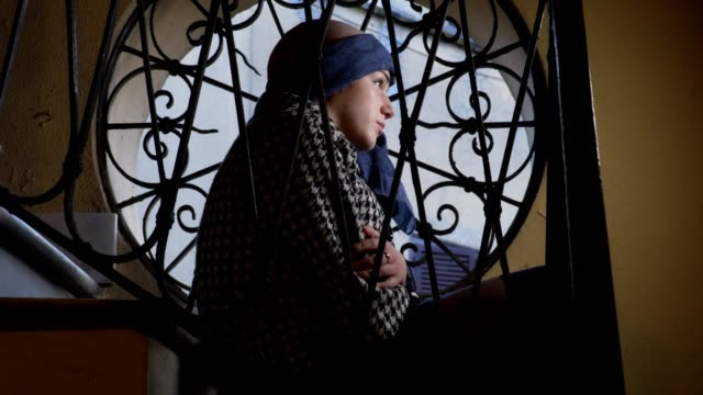 portrait-of-sad-woman-suffering-from-cancer-at-the-window-greets-someone-feebly