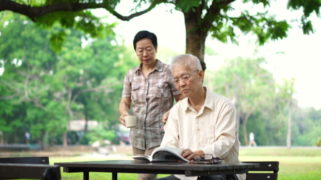 Asian-senior-retire-couple-drink-coffee-and-read-book-in-park