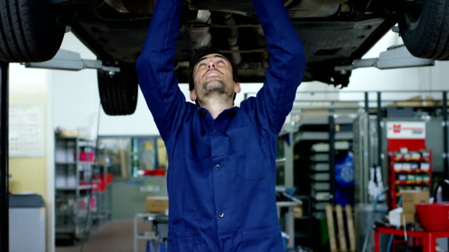Specialist-auto-mechanic-in-the-car-service-checks-the-car-engine-engine-carburetor-Concept:-repair-of-machines-fault-diagnosis-repair-specialist-technical-maintenance-and-on-board-computer-
