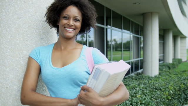 Portrait-of-African-American-female-student-holding-workbook