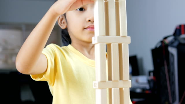 Cerrar-tiro-niña-asiática-jugando-juguetes-de-madera-ladrillo
