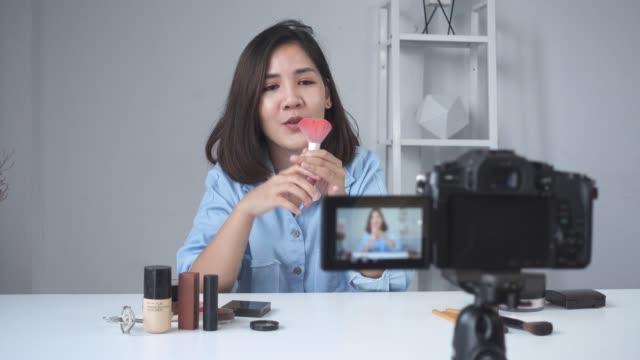 Feliz-sonriente-blogger-mujer-o-belleza-asiática-con-cepillo-y-cámara-de-grabación-de-video-y-agitando-la-mano-en-casa-Concepto-de-belleza-videoblog-blog-personas-Carro-de-tiro-