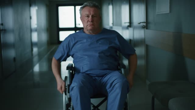 In-the-Hospital-Front-View-Following-Shot-of-the-Elderly-Man-in-the-Wheelchair-Moving-through-the-Hallway-