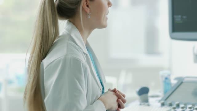 Im-Krankenhaus-Nahaufnahme-von-der-Geburtshelfer-mit-Wandler-für-Ultraschall-/-Ultraschall-Screening-/-Scan-Bauch-der-schwangeren-Frau-