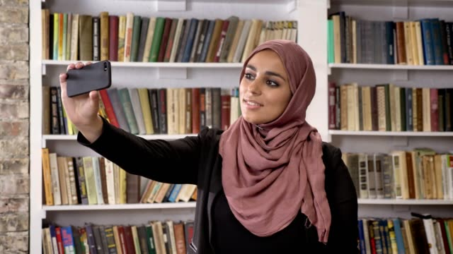 Joven-musulmanes-mujeres-bellas-hijab-tomar-selfie-luego-mirando-en-el-teléfono-y-viendo-fotos-en-la-biblioteca-sonriendo