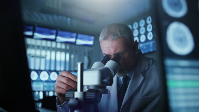 Senior-Medical-Research-Scientist-Looking-under-the-Microscope-in-the-Laboratory-Neurologist-Solving-Puzzles-of-the-Mind-and-Brain-In-the-Laboratory-with-Multiple-Screens-Showing-MRI-/-CT-Brain-Scan-Images-