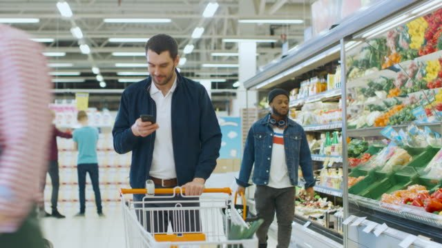 At-the-Supermarket:-Handsome-Man-with-Smartphone-Pushes-Shopping-Cart-Walks-Through-Fresh-Produce-Section-of-the-Store-Chooses-Some-Products-Other-Customers-Purchasing-Products-
