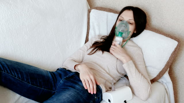 Use-nebulizer-and-inhaler-for-the-treatment-Young-woman-inhaling-through-inhaler-mask-lying-on-the-couch-Front-view-