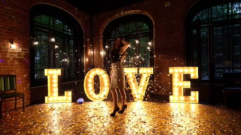 Beautiful-girl-posing-against-a-background-of-shining-letters