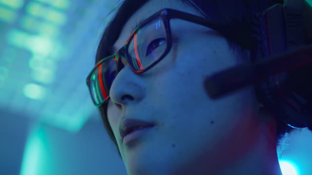 Niedrigen-Winkel-Schuss-der-ostasiatischen-Pro-Gamer-sprechen-in-Mikrofon-auf-seine-Headsphones-Mit-Freunden-chatten-oder-Befehls-zu-seinem-ausgezeichneten-Team-