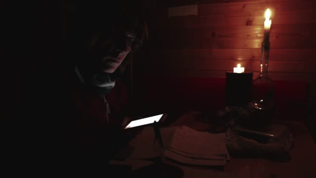 Woman-using-smartphone-hand-writing-paper-candle-light-in-dark-room