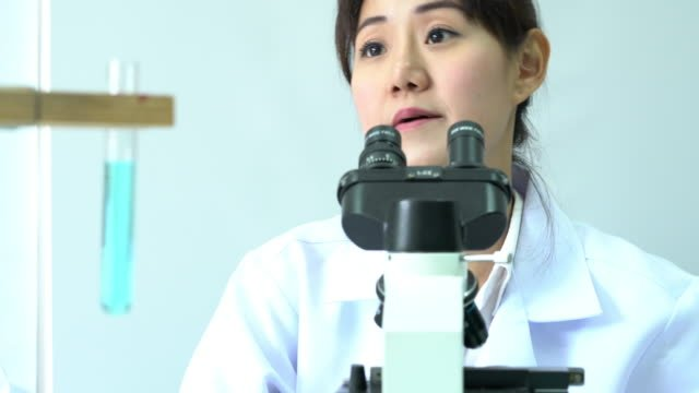 Female-scientists-looking-through-microscope-and-observe-in-modern-laboratory-or-medical-center-Concept-of-science-testing-development-and-lab-industry-